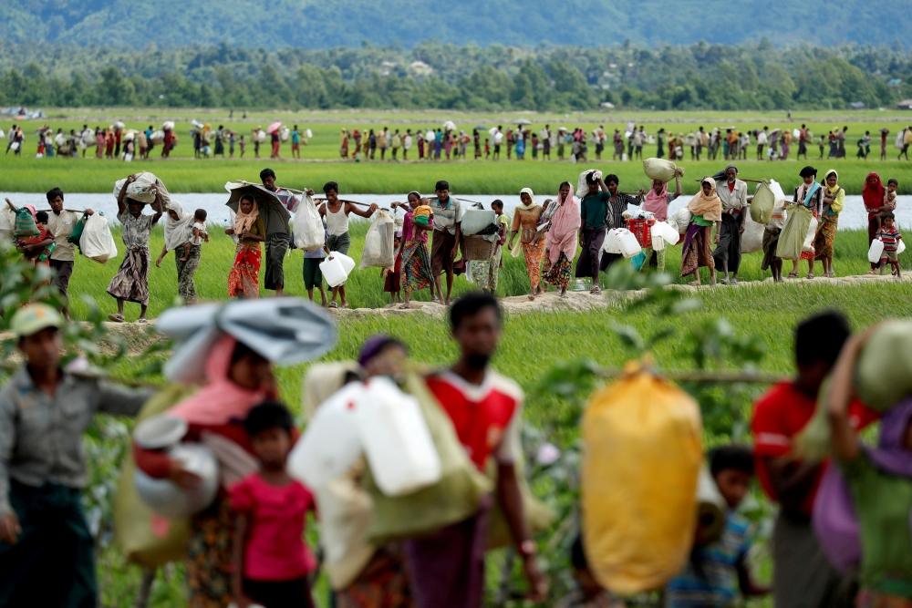 Rohingya refugees, who crossed the border from Myanmar two days before, walk after they received permission from the Bangladeshi army to continue on to the refugee camps, in Palang Khali, near Cox's Bazar, Bangladesh October 19, 2017. -Reuters