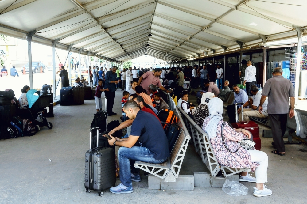 Passengers wait for their flights at Mitiga International Airport in Libya's capital Tripoli on Saturday, after a rocket hit the airport which suspended flights. — AFP