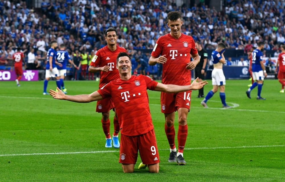 Bayern Munich's Polish forward Robert Lewandowski celebrate scoring his third goal wiht his teammates during the German first division Bundesliga football match FC Schalke 04 FC Bayern Munich in Gelsenkirchen, western Germany, on Saturday. — AFP