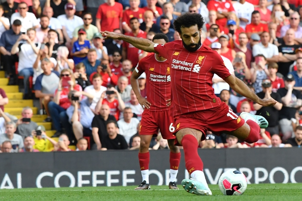 Liverpool's Egyptian midfielder Mohamed Salah shoots to score their second goal from the penalty spot during the English Premier League football match between Liverpool and Arsenal at Anfield in Liverpool, north west England, on Saturday. — AFP