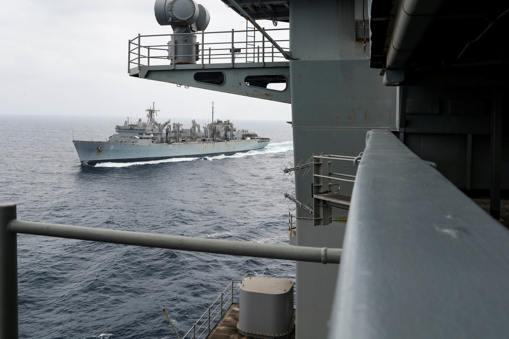 The aircraft carrier USS Abraham Lincoln (CVN 72) breaks away from the fast combat support ship USNS Arctic (T-AOE 8) after a replenishment-at-sea, in Gulf.