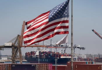 In this file photo taken on August 1, 2019 the US flag flies over a container ship unloading it's cargo from Asia, at the Port of Long Beach, California. -Courtesy photo