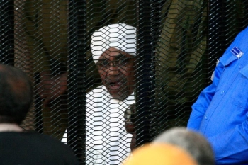 Sudan's deposed military ruler Omar Al-Bashir sits in a defendant's cage during his corruption trial in Khartoum on Saturday. -AFP