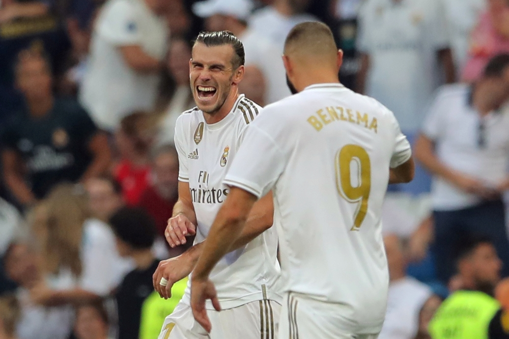 Real Madrid's Karim Benzema celebrates scoring their first goal with Gareth Bale. REUTERS