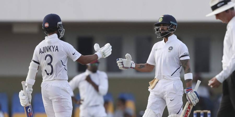 India's captain Virat Kohli, right, is greeted by teammate Ajinkya Rahane after scoring a half century against West Indies during day three of the first Test cricket match at the Sir Vivian Richards cricket ground in North Sound, Antigua and Barbuda, on Saturday. — Courtesy photo