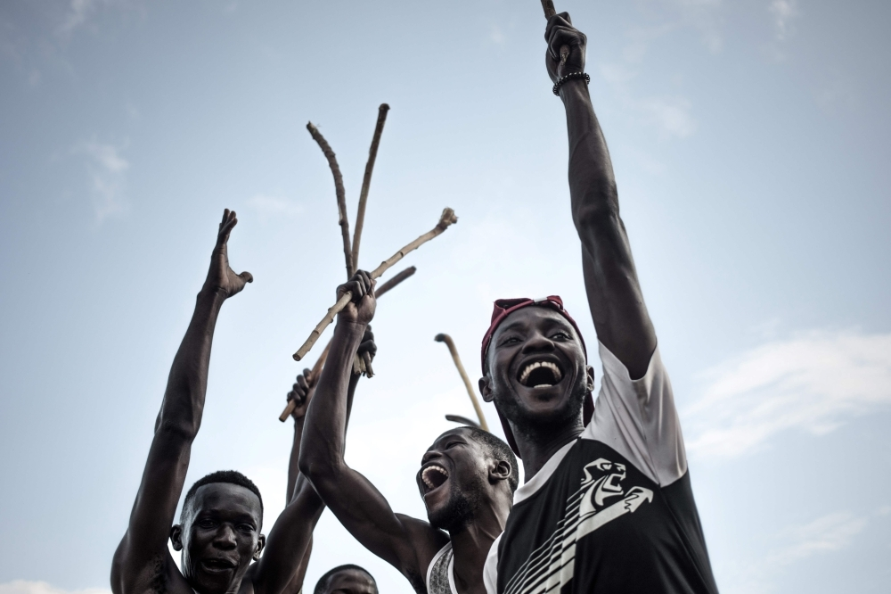 Ngbaba players hold wooden sticks before a game in Bangui, on August 8, 2019. -AFP