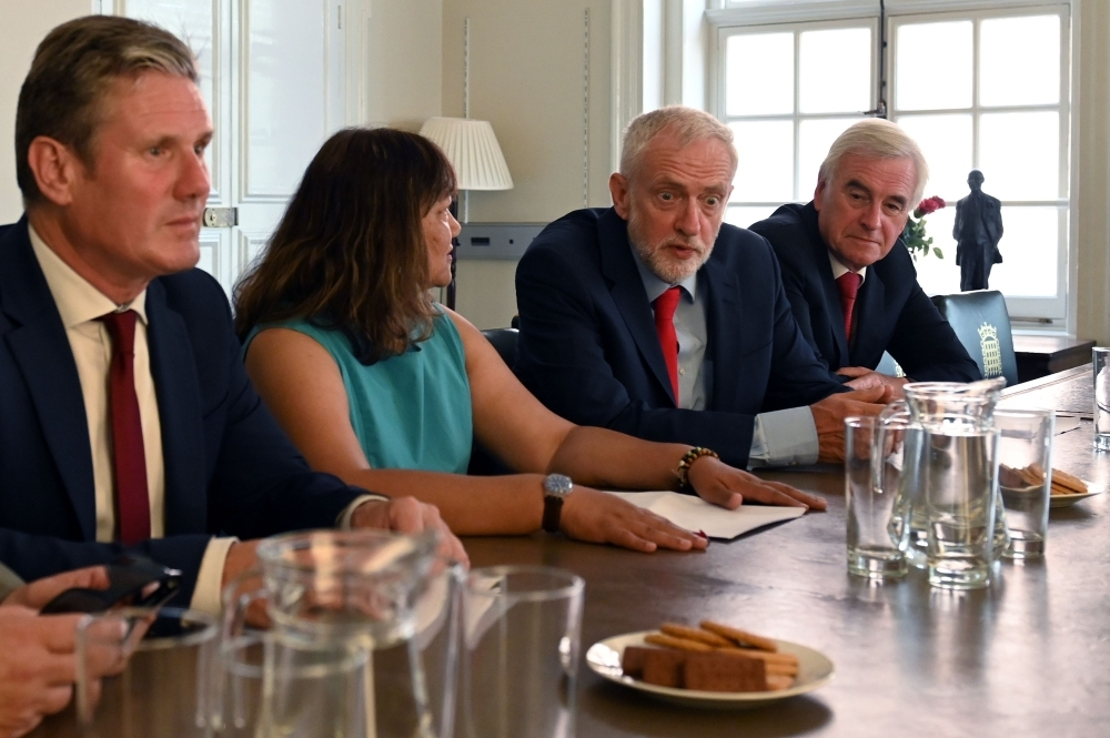 Britain's opposition Labour Party leader, Jeremy Corbyn, second right, sits with members of his shadow cabinet as they pose for a photograph while preparing to meet with leaders of Britain's other political parties to discuss options for Brexit, in Portcullis House, central London, on Tuesday. — AFP