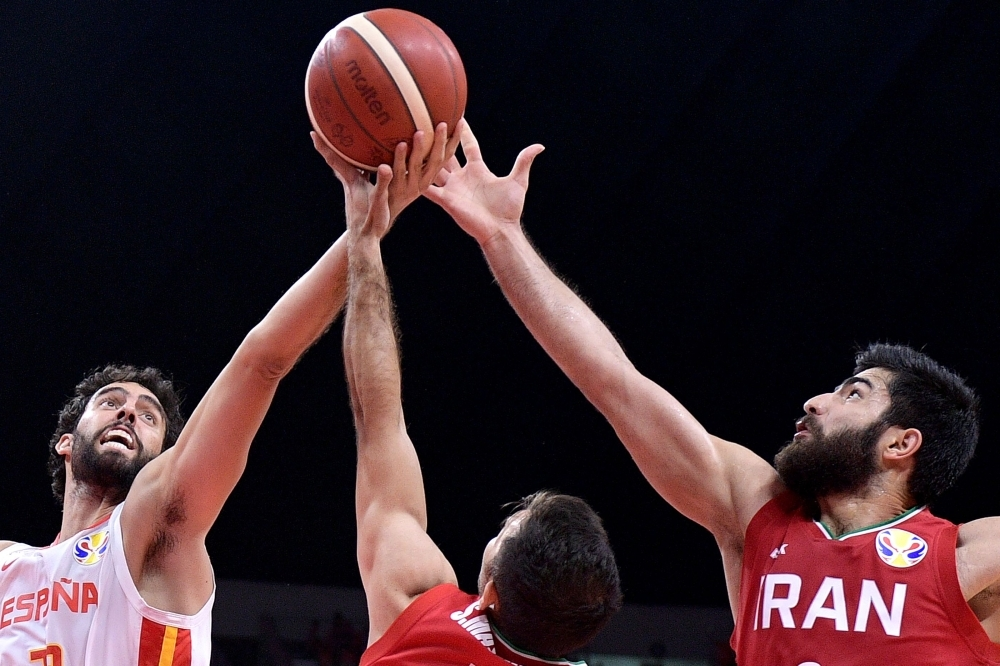 Spain's Javier Beiran (L) fights for the ball with Iran's Behnam Yakhchali (R) and Iran's Sajjad Mashayekhi during the Basketball World Cup Group C game between Spain and Iran in Guangzhou on Wednesday. — AFP