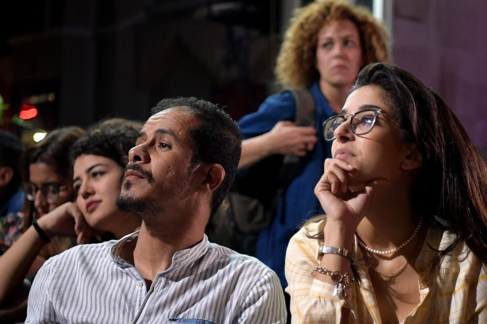 Tunisian people watch the Presidential TV debate in a cafe on Saturday in Tunis. -AFP