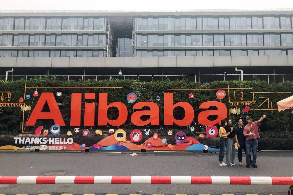 This photo taken on Wednesday shows people taking photos at Chinese e-commerce giant Alibaba's headquarters in Hangzhou in China's eastern Zhejiang province. — AFP