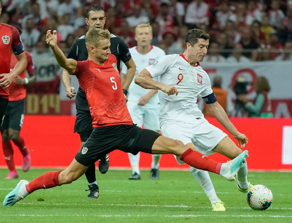 Poland's forward Robert Lewandowski and Austria's Defender Stefan Posch vie during the UEFA Euro 2020 Group G qualification football match Poland v Austria in Warsaw, Poland, on Monday. — AFP
