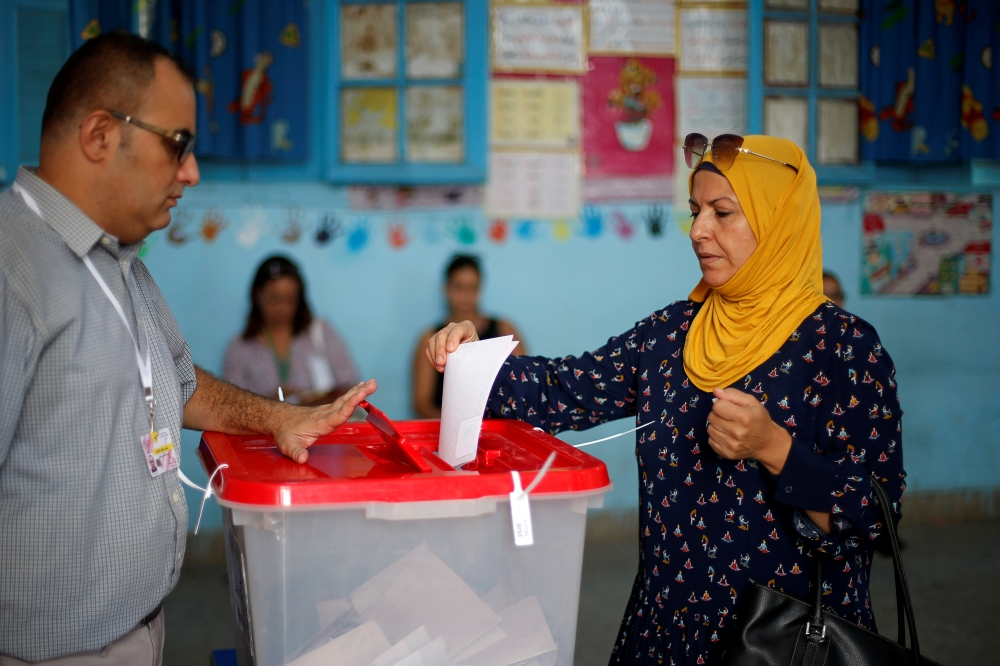 A woman casts her vote in a polling station during presidential election in Tunis, Tunisia on Sunday. -Reuters