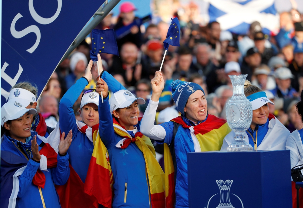 Team Europe celebrates in front of the trophy after winning the Solheim Cup at Gleneagles, Britain, on Sunday. — Reuters