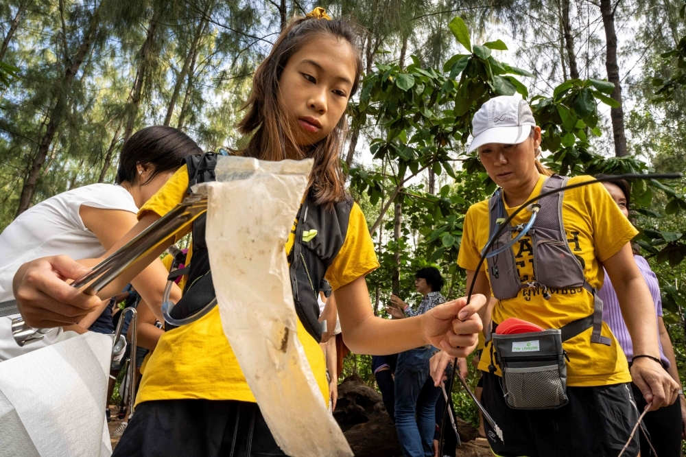 In this picture taken on August 25, 2019, 12-year-old Ralyn Satidtanasarn, known by her nickname Lilly, collects plastic waste during the Trash Hero cleaning initiative at the Khung Bang Kachao urban forest and beach in Bangkok. -AFP