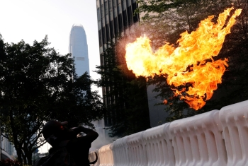 An anti-government protester throws a Molotov cocktail during a demonstration near Central Government Complex in Hong Kong on Sunday. -Reuters