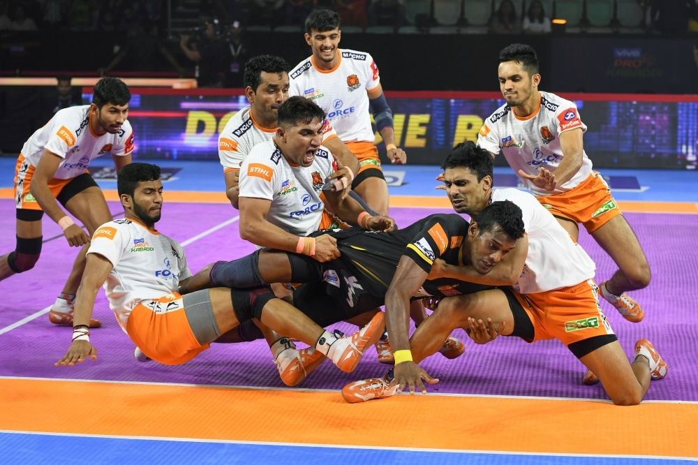 In this photograph taken on August 30, 2019, players of Puneri Paltan hold onto India's Siddharth Desai (C), raider of the Telugu Titans, during the match between Telugu Titans and Puneri Paltan in the Pro Kabaddi League at Thyagaraj Sports Complex in New Delhi. -AFP