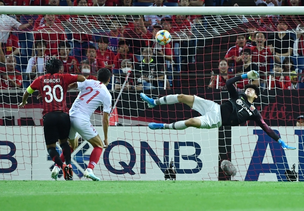 Urawa Reds forward Shinzo Koroki (L) shoots to score a goal during the AFC Champions League football quarterfinals second leg match between Urawa Reds of Japan and Shanghai SIPG of China at the Saitama Stadium 2002 in Saitama, on Tuesday. — AFP