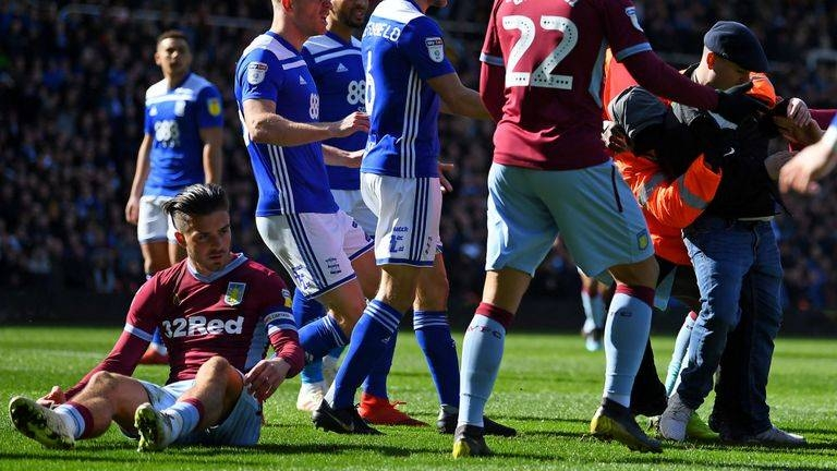 A fan is wrestled to the ground after punching Jack Grealish during the match between Birmingham City and Aston Villa at St Andrew's. — Courtesy photo