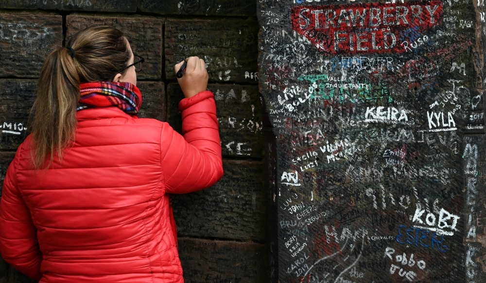 Visitors write on the wall alongside the gates to Strawberry Field in Liverpool, northwest England on Wednesday. Beatles fans can now take a trip through the childhood sanctuary of John Lennon that inspired seminal song