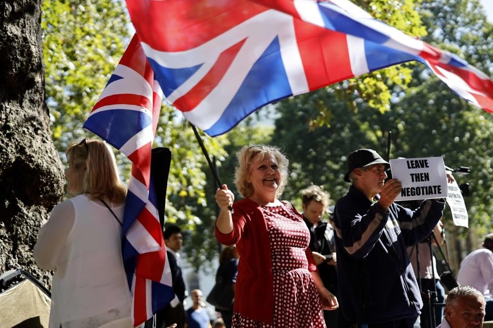 Pro-Brexit demonstrators wave the Union flag and hold placards outside the Supreme Court in central London, on the second day of the hearing into the decision by the government to prorogue parliament on Wednesday. — AFP
