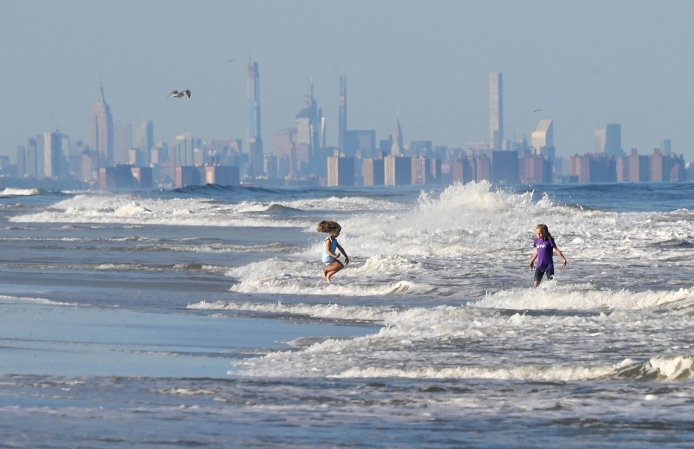 Children jump in the waves at the beach in front of the skyline of Lower Manhattan in Long Branch, New Jersey, in this Sept. 17, 2019 file photo. — AFP