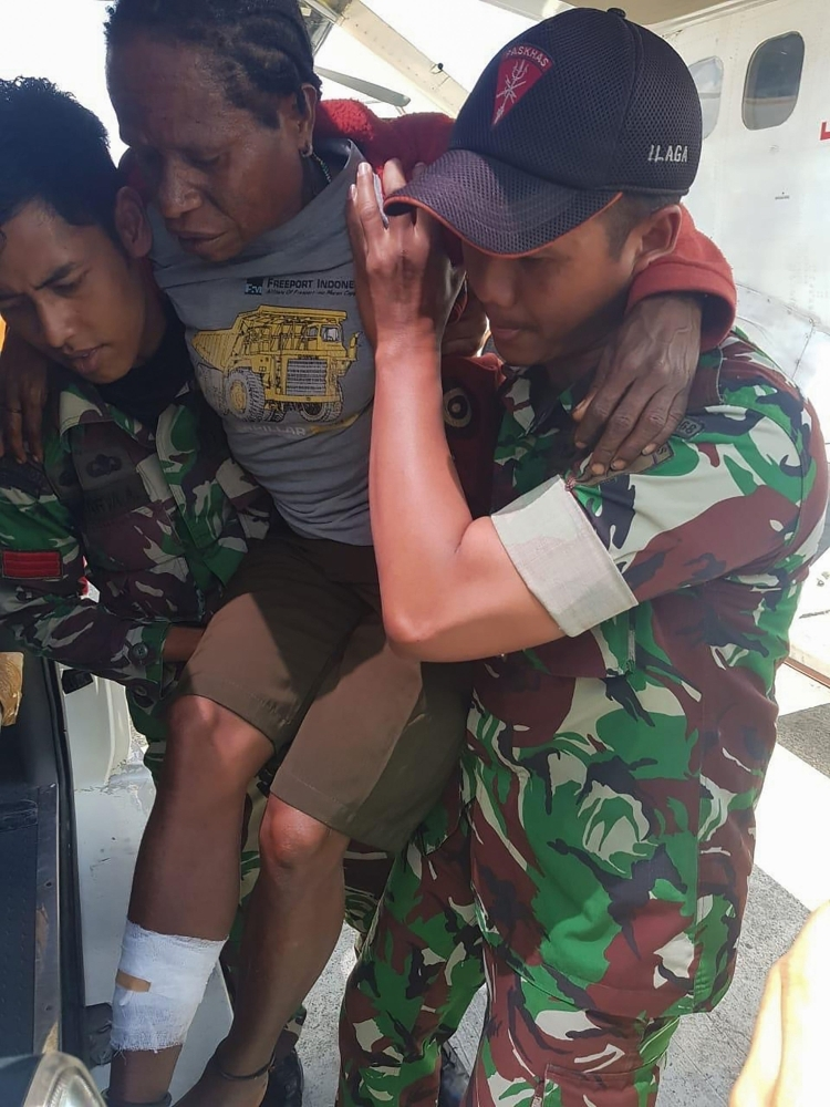 This handout picture by the Indonesian National Armed Forces (TNI) shows Indonesian soldiers carrying a man with a gunshot wound in Ilaga, Papua.  A toddler and teenager were among three people killed in a gunfight between security forces and independence-seeking rebels in Indonesia's restive Papua region, the military said on Tuesday. — AFP