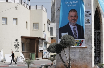 An Arabic-language election banner displaying a portrait of Arab Israeli candidate Waleed Taha is pictured in the Israeli town of Kfar Qassem, on Wednesday. The Joint List coalition of Arab Israeli parties reportedly won 12 seats in Israel's parliamentary elections. — AFP