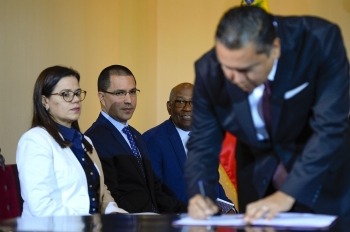 Venezuelan Foreign Minister Jorge Arreaza (2nd L) looks at opposition member Javier Bertucci during the signing of the dialogue agreement between the government and the opposition in Caracas on Wednesday. — AFP