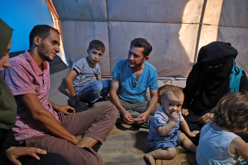 Jaber Karawan, center, and his wife Walaa, right, sit with their children and others inside a shelter at a camp for displaced Syrians in Atme in the northwestern Idlib province, near the border with Turkey, in this Sept. 20, 2019 file photo. — AFP