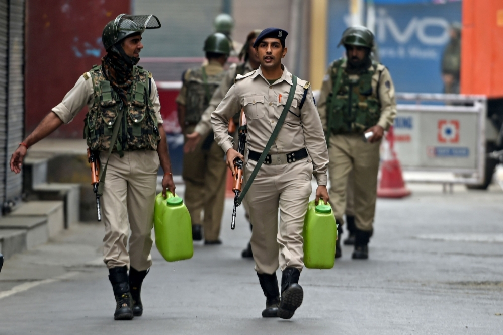Security personnel walk as they carry water cans while strict restrictions are imposed during a lockdown in Srinagar in this Sept. 28, 2019 file photo. — AFP