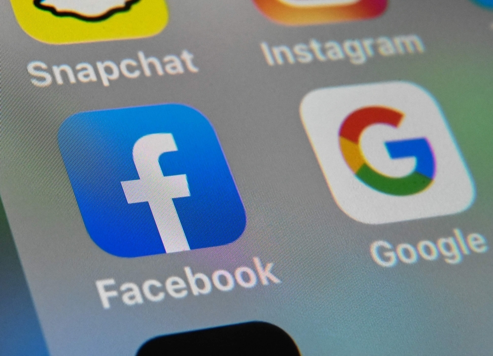 In this file photo taken on Oct. 1, 2019 in Lille shows the logos of mobile apps Facebook and Google displayed on a tablet. Facebook on Thursday launched Threads, an image-centric messaging app designed to weave tight circles of Instagram friends together, while ramping up its challenge to rival Snapchat. Threads is its own separate smartphone app, but ties into lists of
