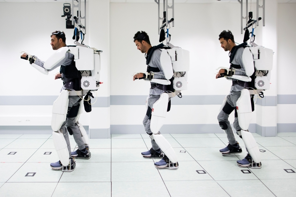 This handout combination of photographs released on Oct. 3, 2019, by Clinatec Endowment Fund (fonds de dotation Clinatec) shows French tetraplegic 'Thibault' as he stands while wearing an exo-skeleton at The University of Grenoble in Grenoble. — AFP