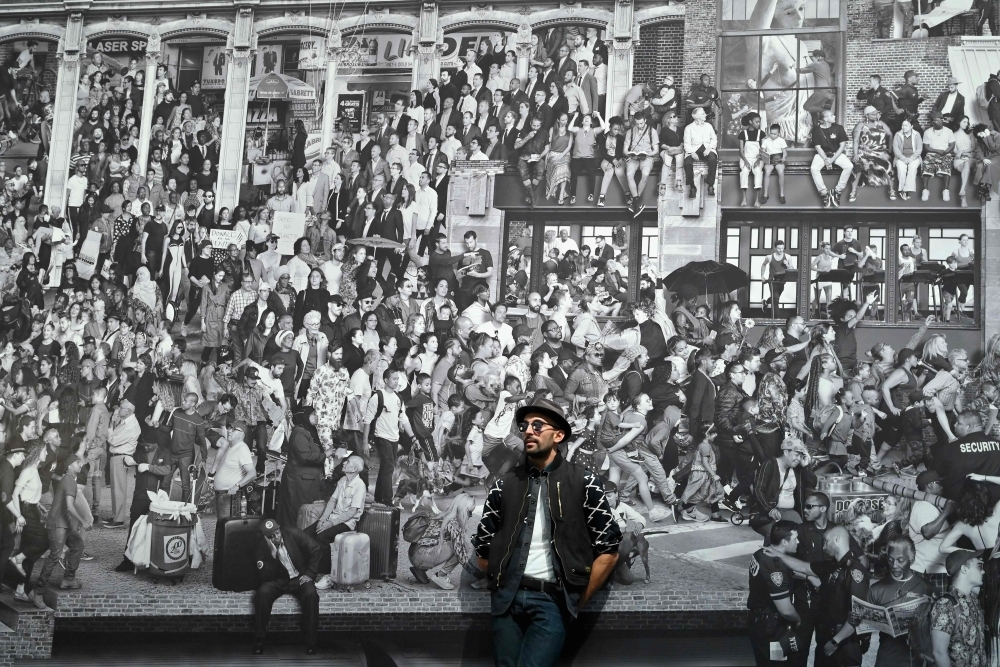 French-born artist JR poses for pictures prior to the opening of his exhibition