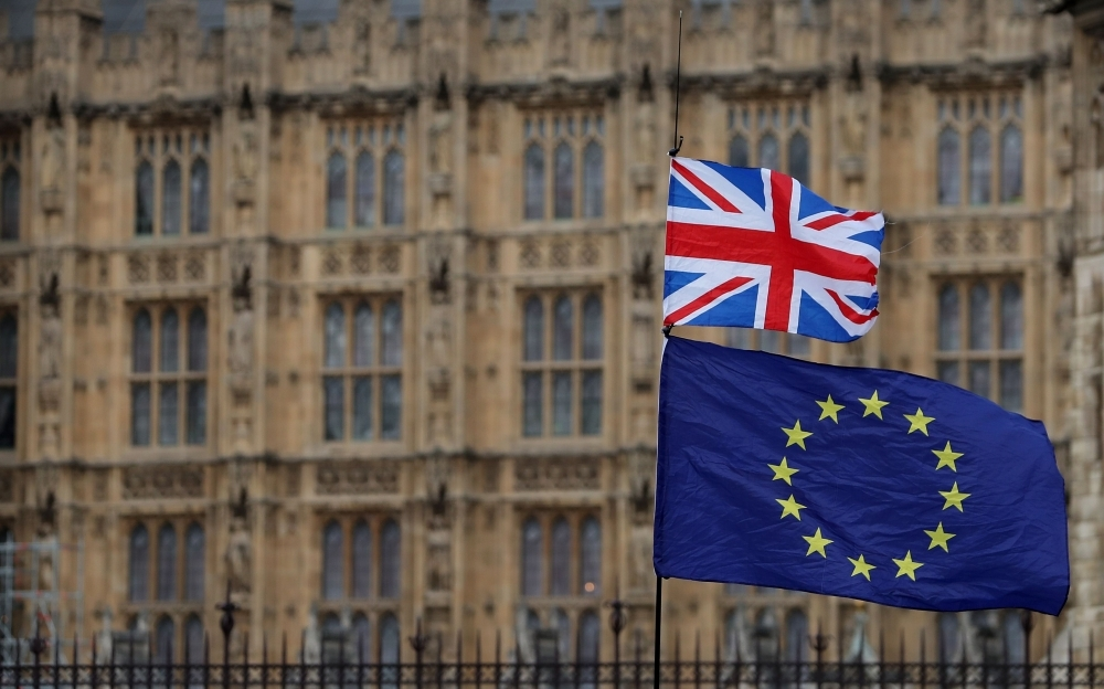 An anti-Brexit activist waves a Union and a European Union flag as they demonstrate outside the Houses of Parliament in central London in this Jan. 23, 2019 file photo. — AFP
