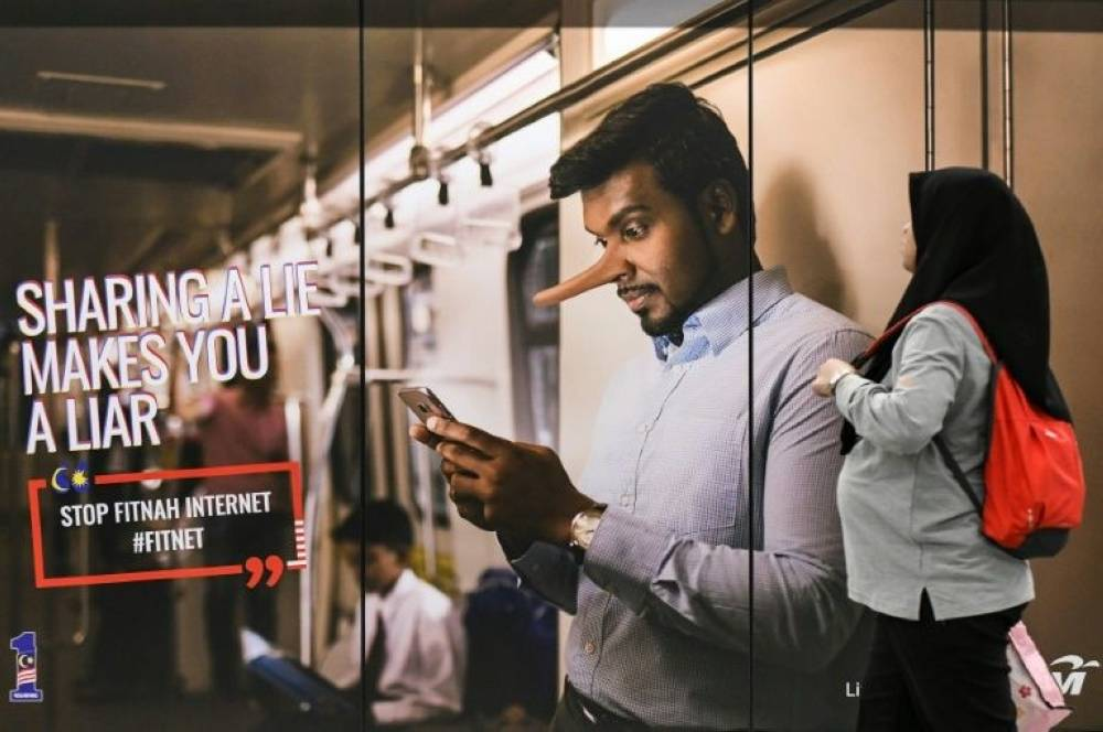 "A commuter walks past an advertisement reading ""Sharing a lie makes you a liar"" at a train station in Kuala Lumpur as the government introduces a bill to combat ""fake news."" -AFP"