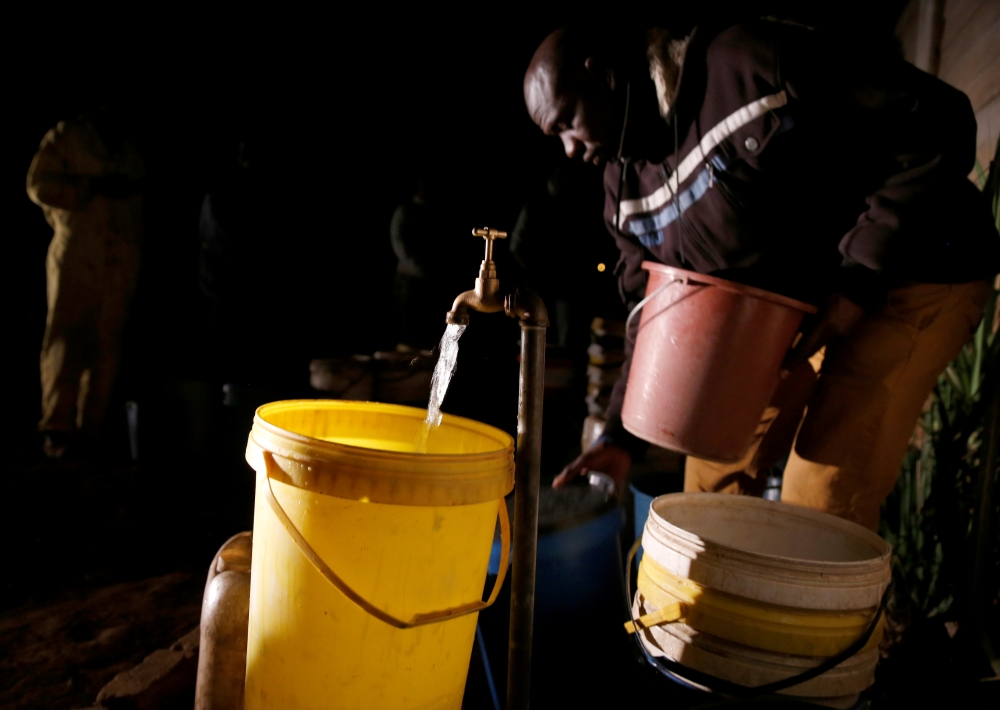 Residents collect water at night from an electric-powered borehole, as the country faces 18-hour daily power cuts, in a suburb of Harare, Zimbabwe, in this July 30, 2019 file photo. — Reuters