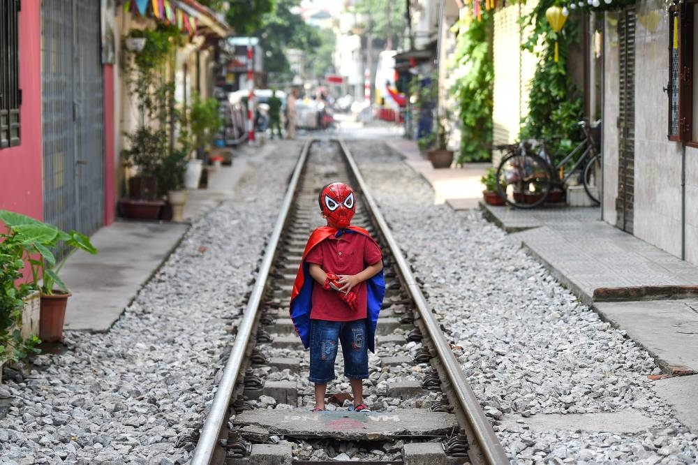 A boy wearing a Spiderman costume stands on Hanoi's popular train street on October 10, 2019 following a municipal authorities order to deal with cafes and