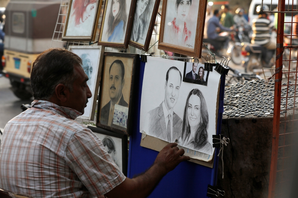 Street artist Mohammad Zaffar, 54, draws a sketch of Britain's Prince William and Catherine, Duchess of Cambridge, ahead of their visit, from a makeshift stall along a sidewalk in Karachi, Pakistan, Friday. — Reuters