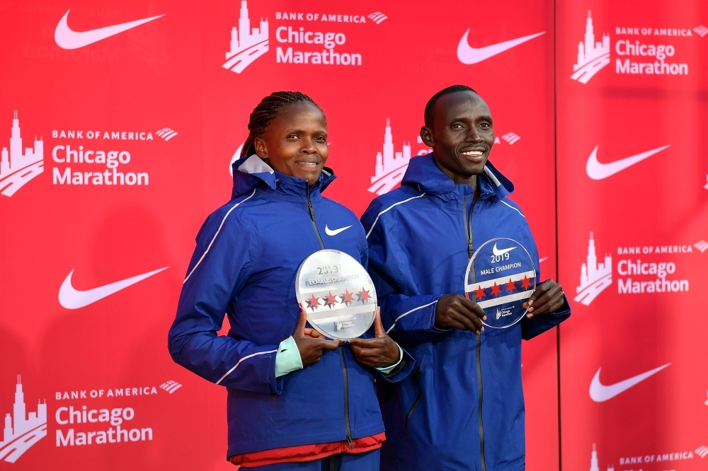 Brigid Kosgei (L) of Kenya and Lawrence Cherono (R) of Kenya pose for a photo after winning the 2019 Bank of America Chicago Marathon in Chicago, Illinois, on Sunday. — AFP