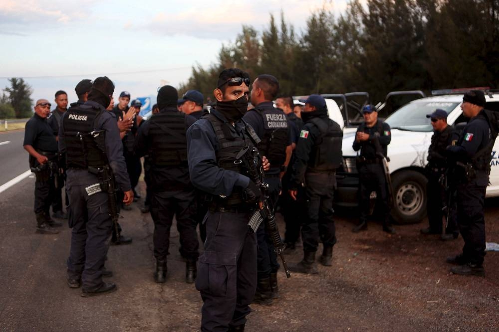 Federal policemen gather outside a ranch where a gunfight between hit-men and federal forces left several casualties in Tanhuato, state of Michoacan, in this May 22, 2015 file photo. — Reuters