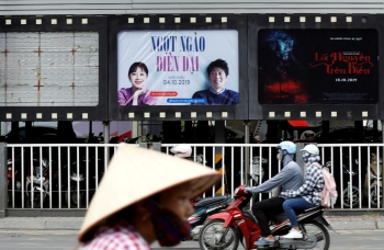 Bikers go past an empty space where a promotional poster for the DreamWorks film