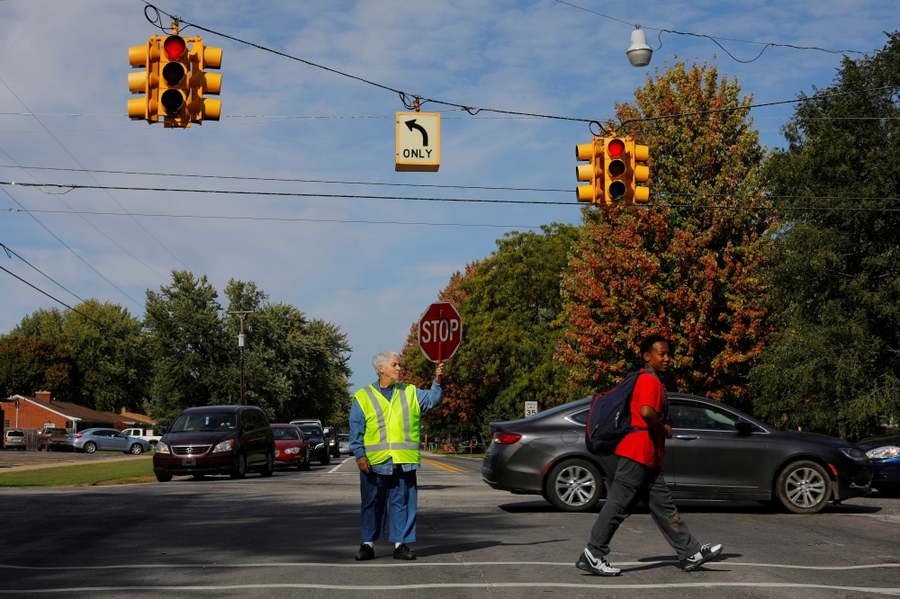 Crossing guard Barbara Elliott helps a student across an intersection in Precinct 7, where the vote was split 876/876 between Donald Trump and Hillary Clinton in 2016, in Saginaw Township, Michigan, in this Oct. 10, 2019 file photo. — Reuters