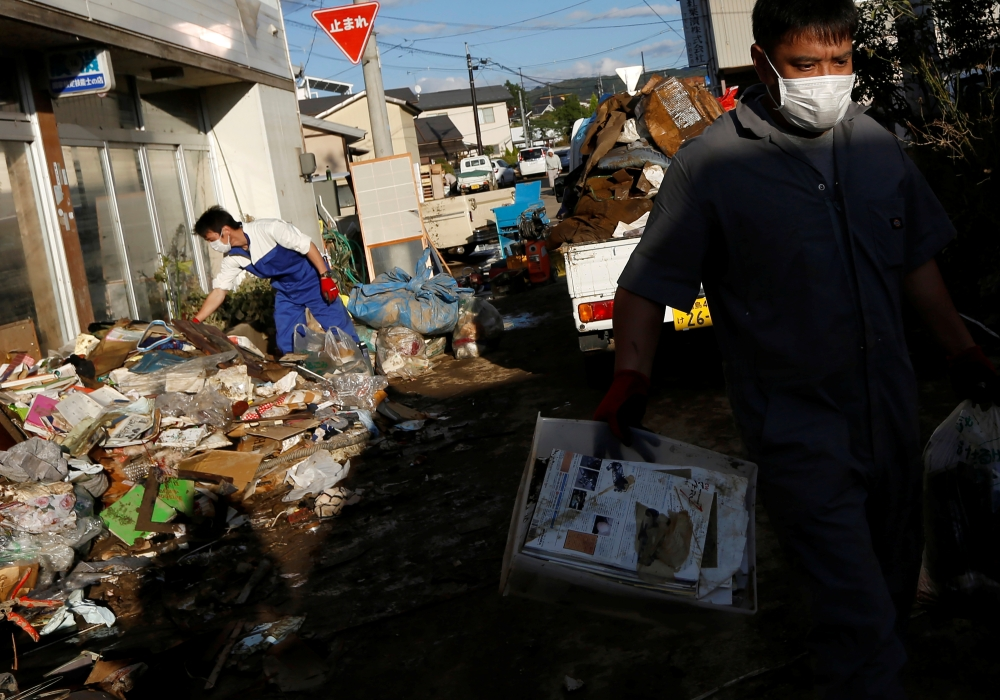 Locals clean a house, in the aftermath of Typhoon Hagibis, in Yanagawamachi district, Date City, Fukushima prefecture, Japan, on Tuesday. — Reuters