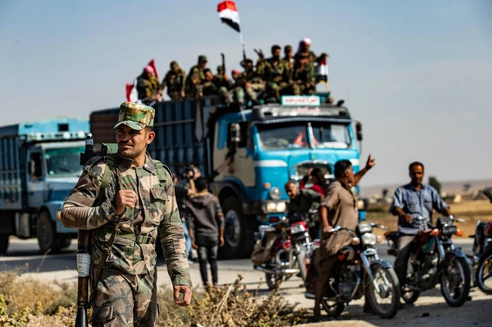 Syrian government forces arrive in the town of Tal Tamr, not far from the flashpoint Kurdish Syrian town of Ras Al-Ain on the border with Turkey, which has been a key target of Turkish forces and their proxies since they launched their military assault, on Tuesday. — AFP