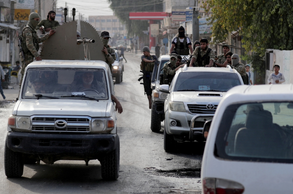 Turkey-backed Syrian rebel fighters ride at the back of a truck mounted with a weapon in the border town of Tal Abyad, Syria, on Tuesday. — Reuters