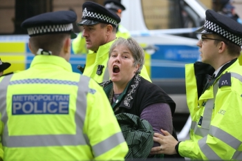 An activist from the Extinction Rebellion climate action movement is detained by police after she locked herself on to the entrance of the building housing the government's Department for Transport in central London on Tuesday. — AFP