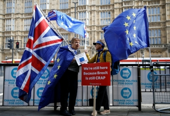 Anti-Brexit protesters hold flags outside the Houses of Parliament in London on Tuesday. — Reuters