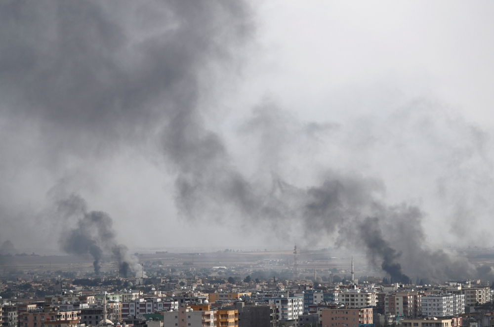 Smoke billows out after Turkish shelling on the Syrian town of Ras Al Ain, as seen from the Turkish border town of Ceylanpinar, in Sanliurfa province, Turkey, on Wednesday. — Reuters
