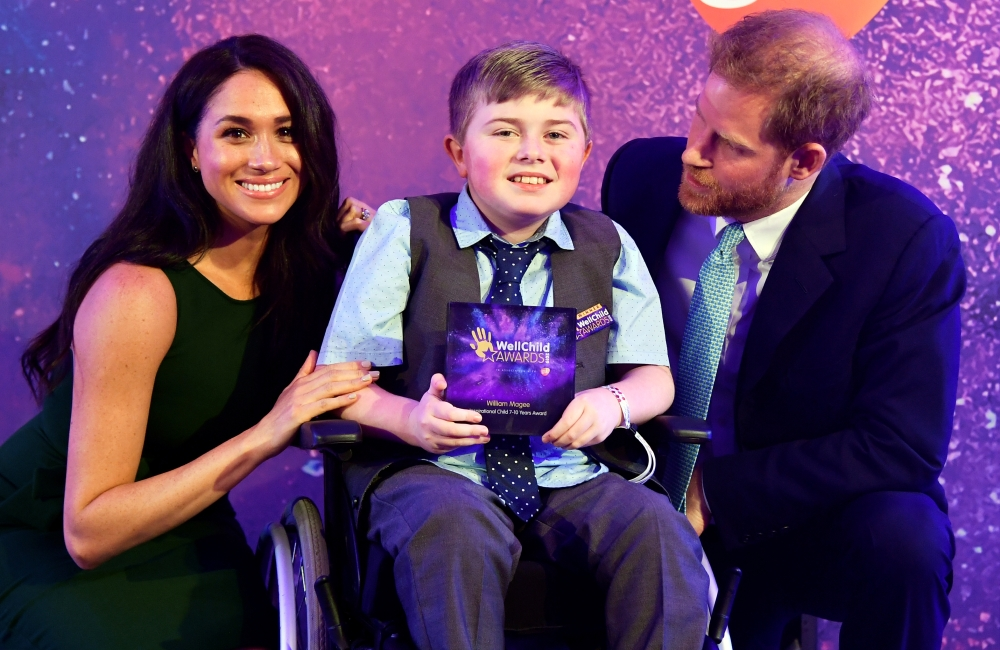 Britain's Prince Harry and Meghan, Duchess of Sussex pose for a photograph with award winner William Magee during the WellChild Awards Ceremony reception in London, Britain, on Tuesday. — Reuters
