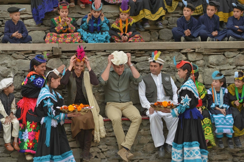 Kalash girls presents traditional hats to Britain's Prince William, center, Duke of Cambridge and his wife Britain's Catherine, fourth left, Duchess of Cambridge during their visit to the Bumburate Valley in Pakistan northern Chitral District on Wednesday. — AFP